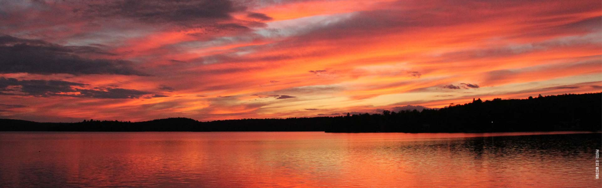 Brilliant orange sunset over a lake in South Algonquin, photo by Jess McComb